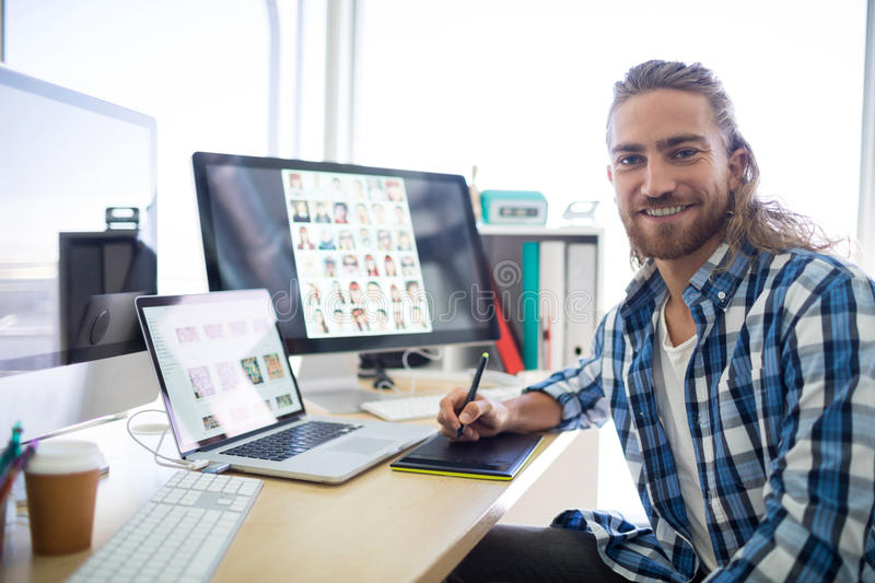 Portrait of male executive sitting at his desk stock photos