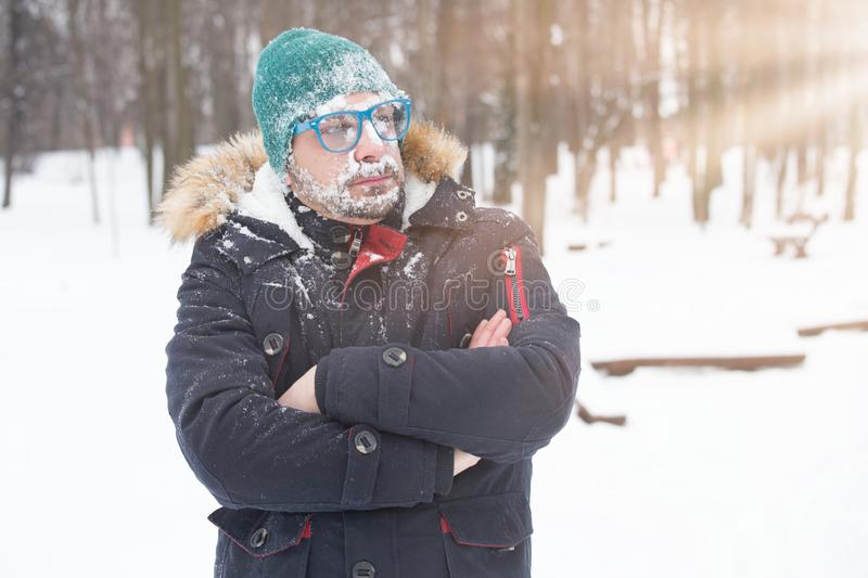 Portrait of male face covered with snow. Crazy, cheerful, funny, comic and emotions. Winter concept royalty free stock image