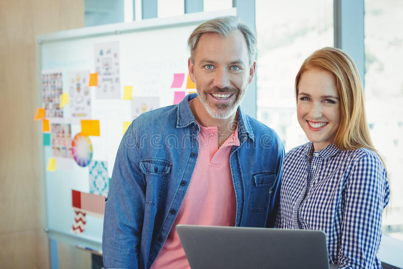 Portrait of male and female executives holding laptop. In office stock photos