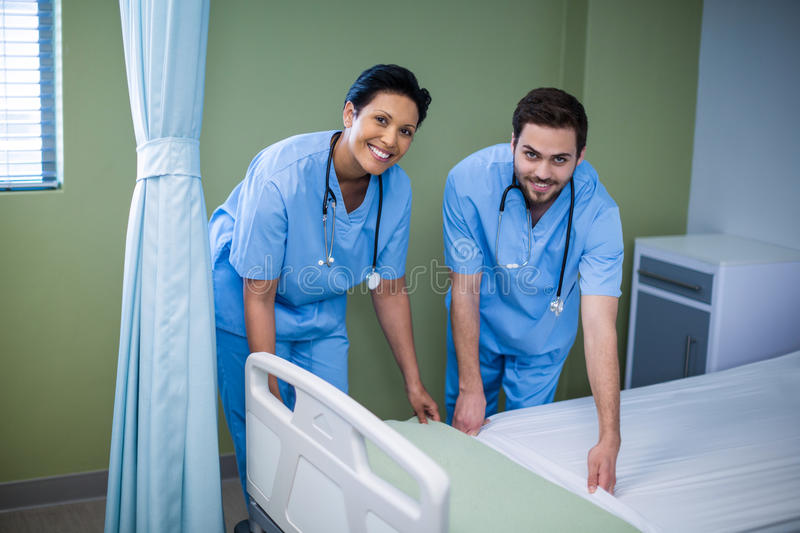 Portrait of male and female nurse preparing bed for patient. In ward stock images