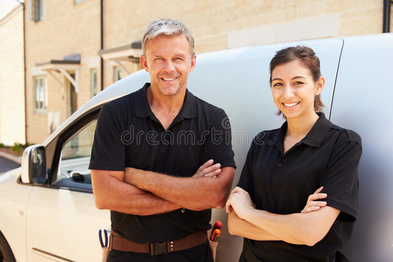 Portrait of male and female trade workers standing by a van stock images