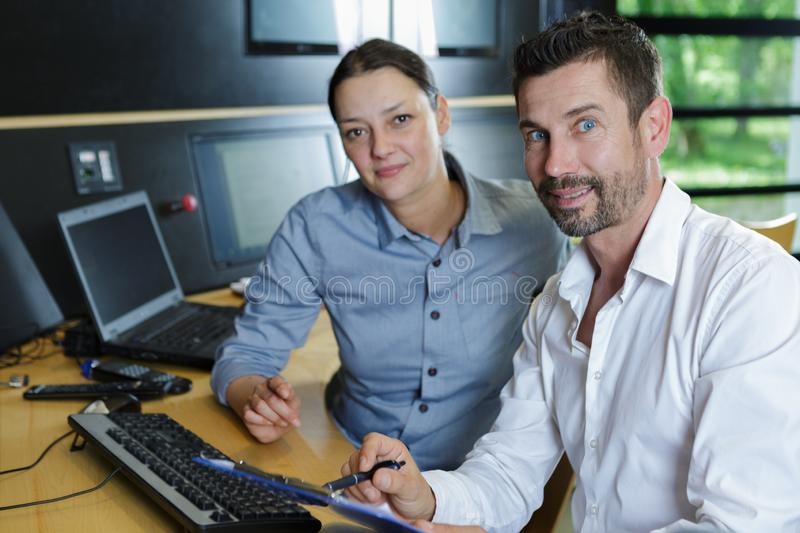 Portrait male and female workers in control center stock photos