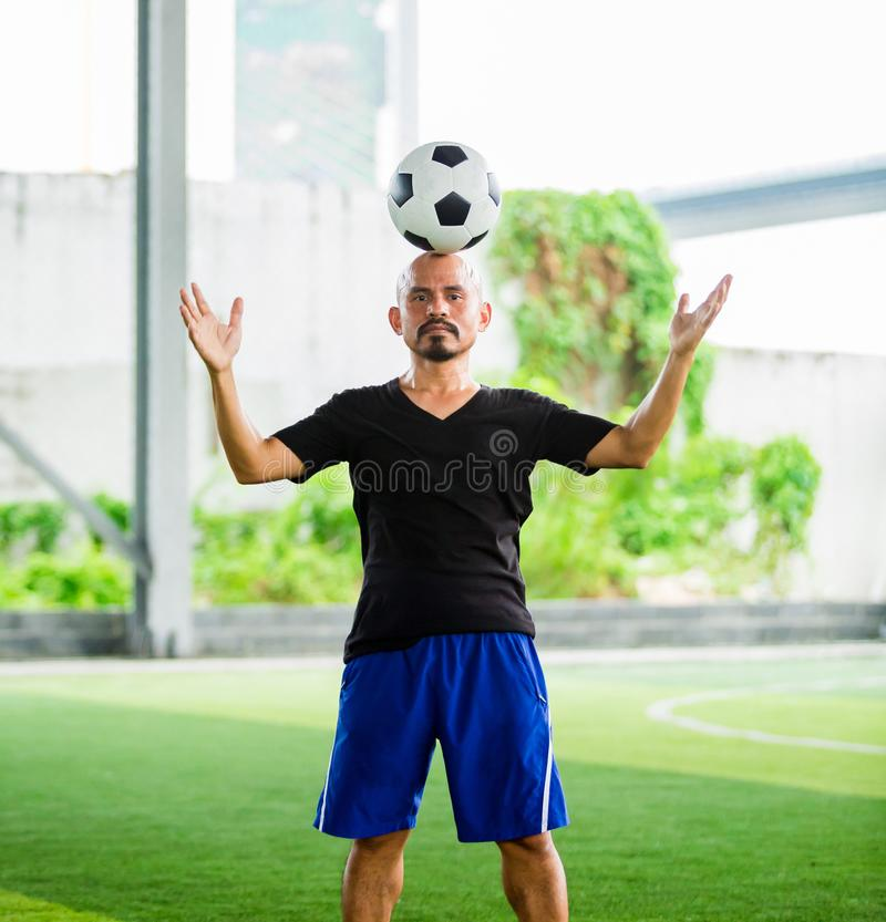 Portrait of a male football player juggling a ball on his head stock photo