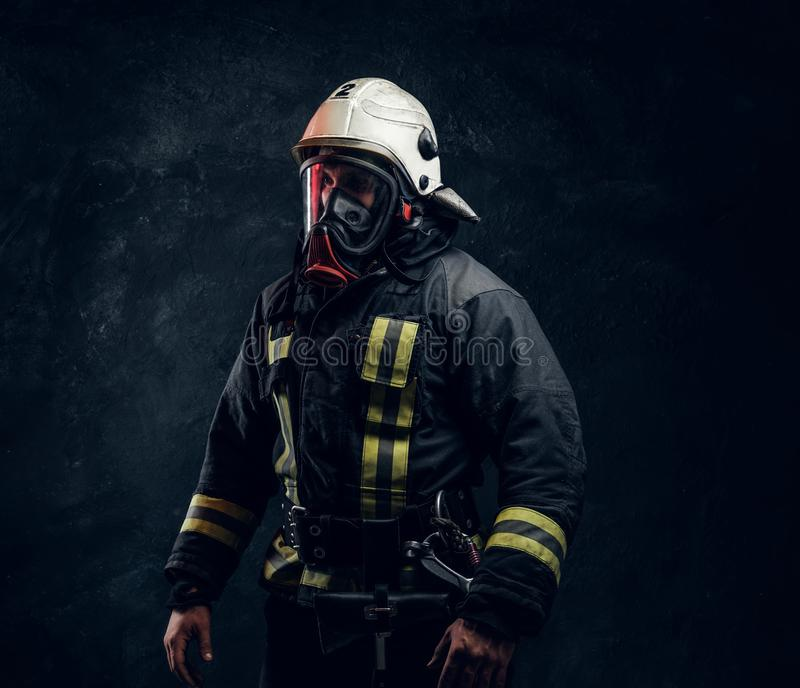 Portrait of a male in full firefighter equipment posing in a dark studio. Portrait of a male in full firefighter equipment. Studio photo against a dark textured royalty free stock images