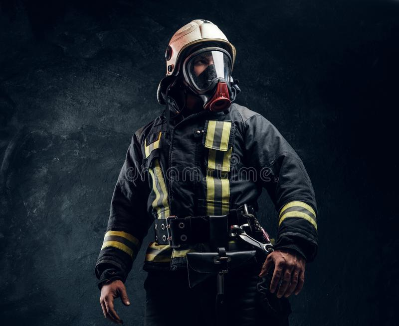 Portrait of a male in full firefighter equipment posing in a dark studio. Portrait of a male in full firefighter equipment. Studio photo against a dark textured royalty free stock image