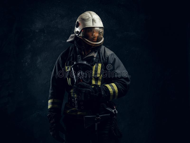 Portrait of a male in full firefighter equipment posing in a dark studio. Portrait of a male in full firefighter equipment. Studio photo against a dark textured royalty free stock photography