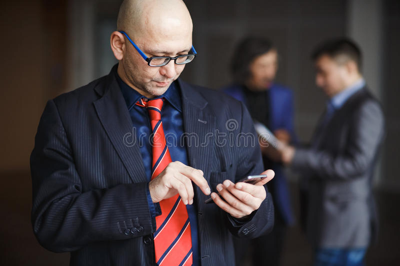 Portrait of male with glasses bald businessman using phone in hand, dressed striped suit and red tie, stands indoors. Portrait of a men with glasses businessman royalty free stock images