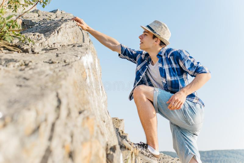 Male hiker climbing up mountain cliff during hiis travel royalty free stock photo