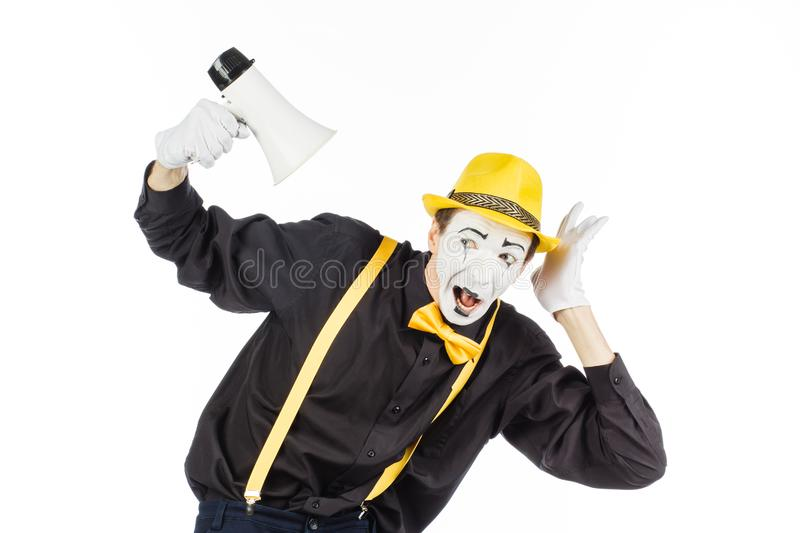 Portrait of a male mime artist, shouting or showing on a megaphone. Isolated on white background. royalty free stock photo