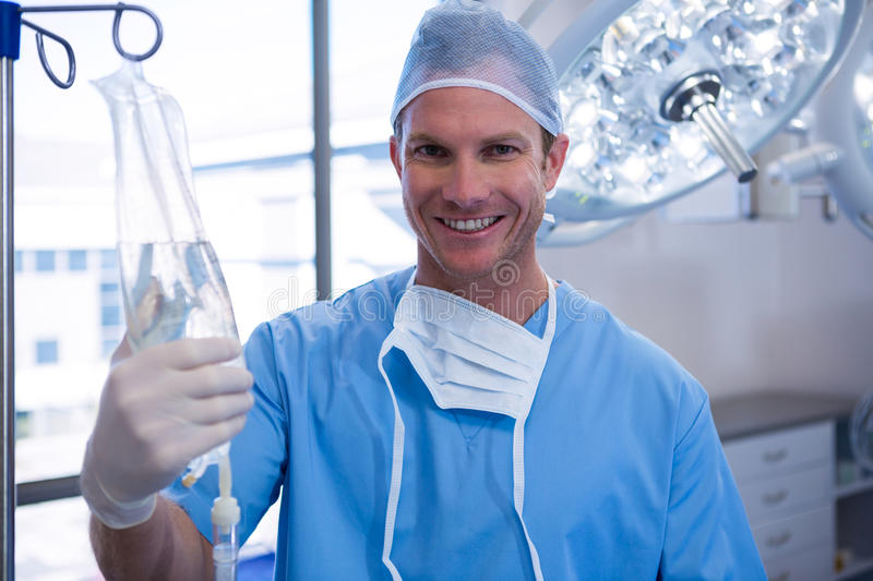 Portrait of male nurse adjusting iv drip in operation theater. At hospital royalty free stock photography