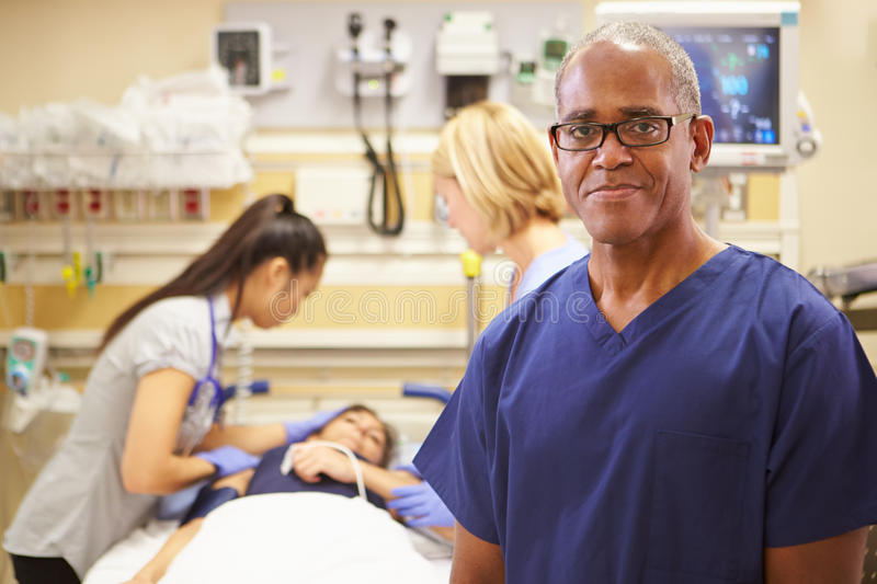 Portrait Of Male Nurse Working In Emergency Room. Looking At Camera With Patient And Doctor In Background stock photography
