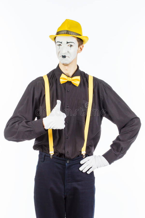 Portrait of a male, pantomime actor looking at camera and showing thumb up. royalty free stock photography