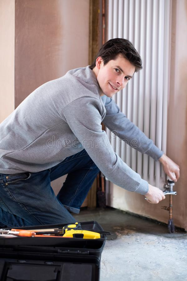 Portrait Of Male Plumber Fitting Vertical Radiator In Room Of House royalty free stock photo