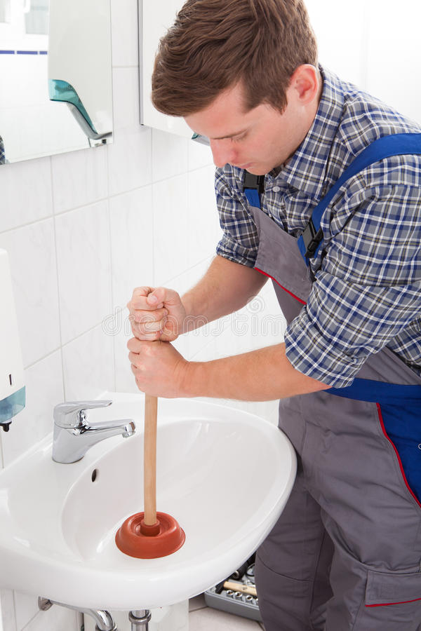 Portrait of male plumber pressing plunger. In sink stock image