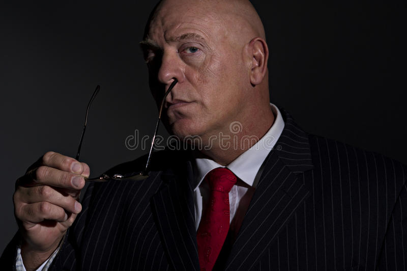 Portrait of male removing eye glasses. Low key portrait of a mature male wearing a pin stripe suit. He is removing his glasses. He resembles a criminal boss, or stock images