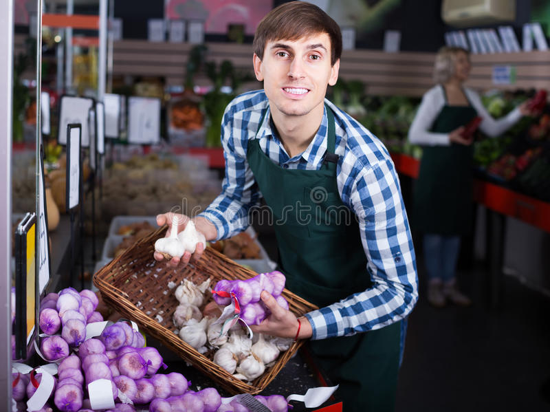 Portrait of male seller with stalks of garlic in grocery royalty free stock photo