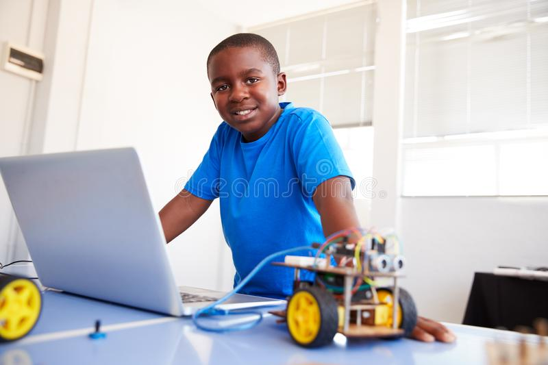 Portrait Of Male Student Building And Programing Robot Vehicle In School Computer Coding Class royalty free stock photo