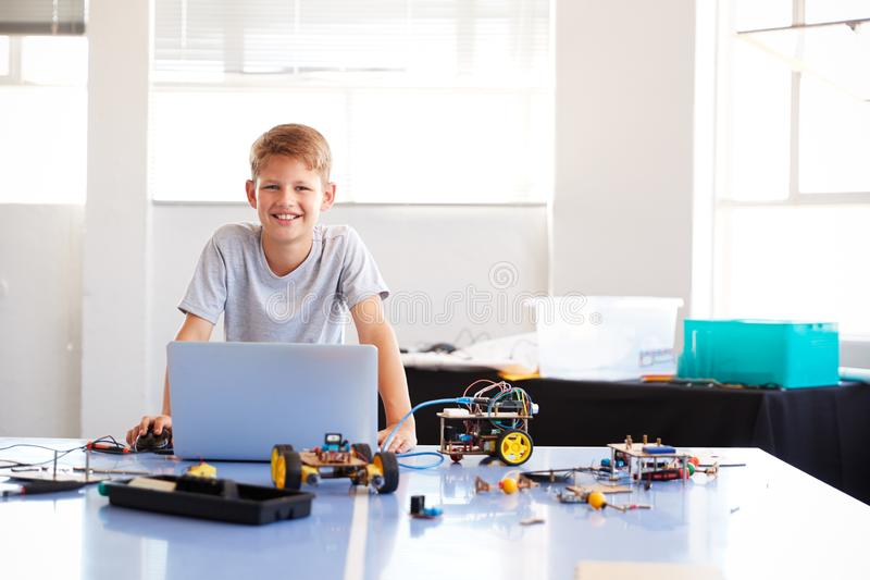 Portrait Of Male Student Building And Programing Robot Vehicle In School Computer Coding Class stock images
