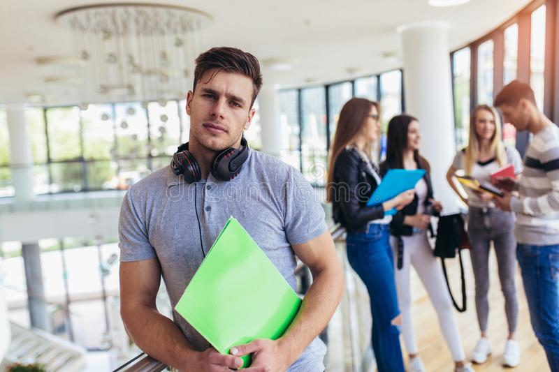 Male student standing wall in corridor of a college. Caucasian male student in university campus stock photos