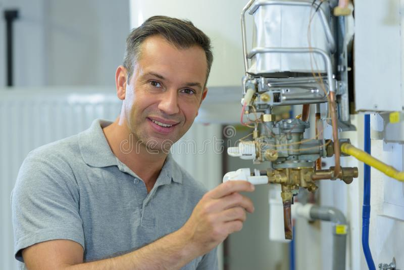 Portrait man adjusting gas boiler royalty free stock photos