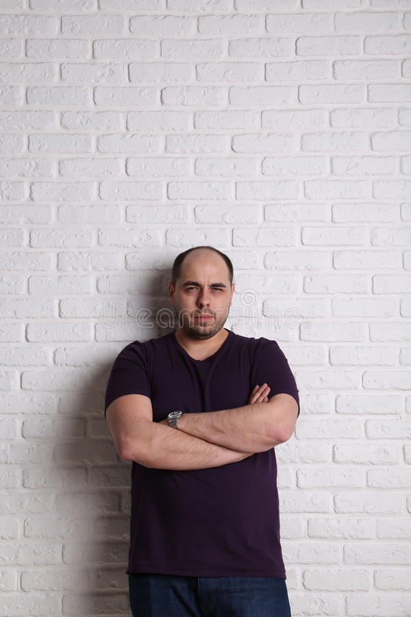 Portrait of a man, arms crossed hands, against white wall stock photography