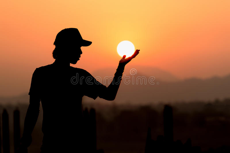 Portrait of man as silhouette and hand holding the sun royalty free stock photos
