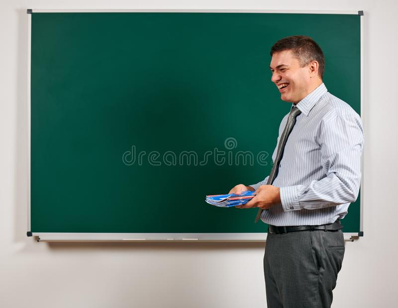 Portrait of a man as a teacher, posing at school board background - learning and education concept royalty free stock image