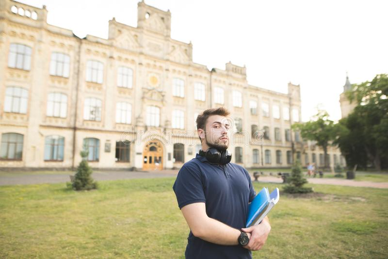 Portrait of a man with a beard standing on a campus with books in his hands and looking at the camera. Student with notebooks on the background of the royalty free stock image