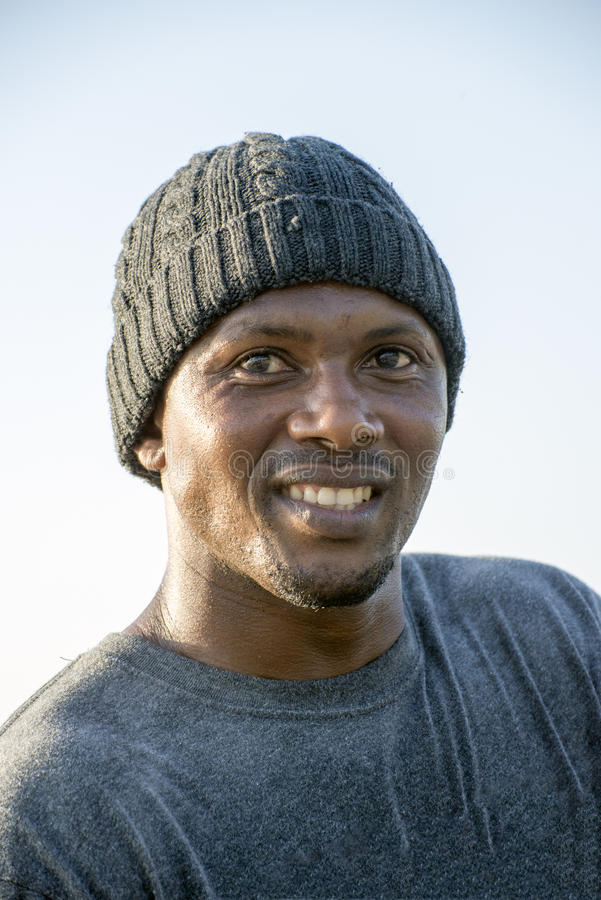 Portrait of man with Beeny on head. A portrait of a smiling African man with a grey t shirt and a grey woolen beany on his head stock image