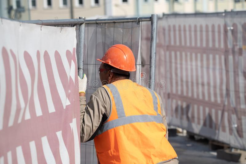 Portrait of a man from behind in a construction, orange helmet against the background of a construction site. Concept architecture stock photography