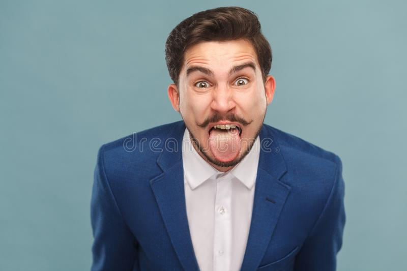 Portrait of man with big eyes, tongue out and shout. Business people concept, richly and success. Indoor, studio shot on light blue background stock photos