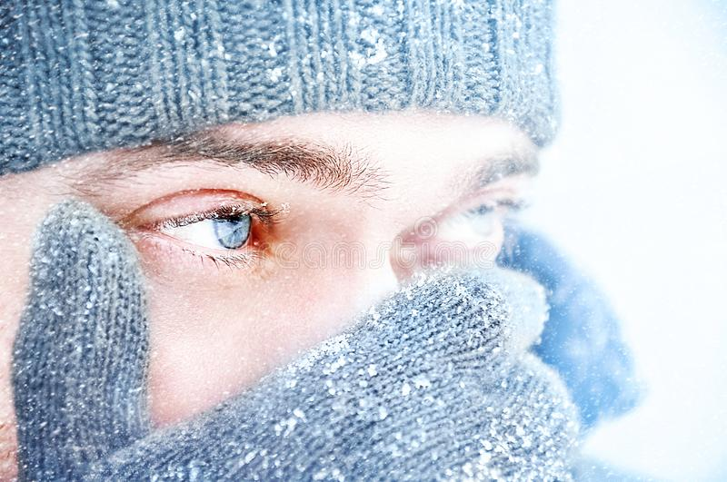 Portrait of a man with blue eyes against a background of falling snow. Beautiful snowy weather. Snowing. Selective focu. S royalty free stock image