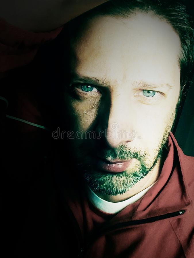 Portrait of a man with blue eyes - photography. The portrait of a young bearded man with blue eyes - photograph stock photo