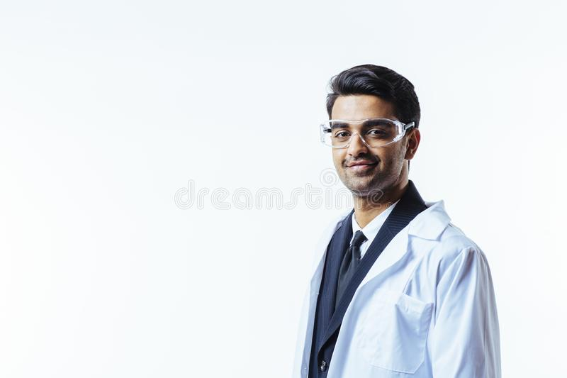 Portrait of a man in business suit, lab coat and protective glasses. stock photography