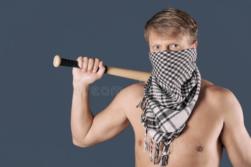 Portrait of a shirtless man in checkered scarf holding a baseball bat symbolizing crime on blue background. Portrait of a man in checkered scarf holding a stock image