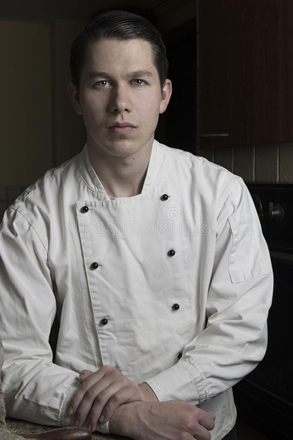 Portrait of nice and attractive man chef in uniform in his restaurant. Man chef standing in kitchen and posing to camera. stock photography