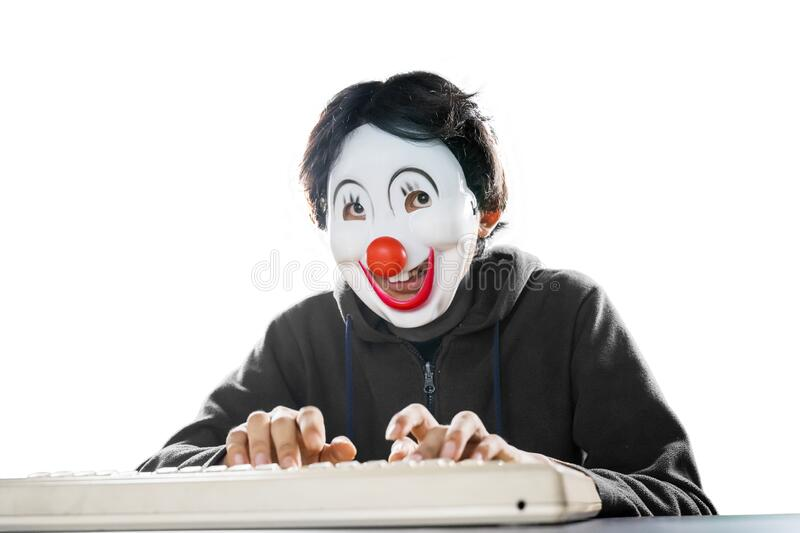 Portrait of man in clown mask typing on desktop stock photos