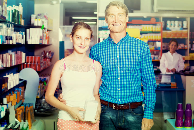 Portrait of man with daughter teenager shopping medicine in drug. Portrait of european men with daughter teenager shopping medicine in drug store stock photography