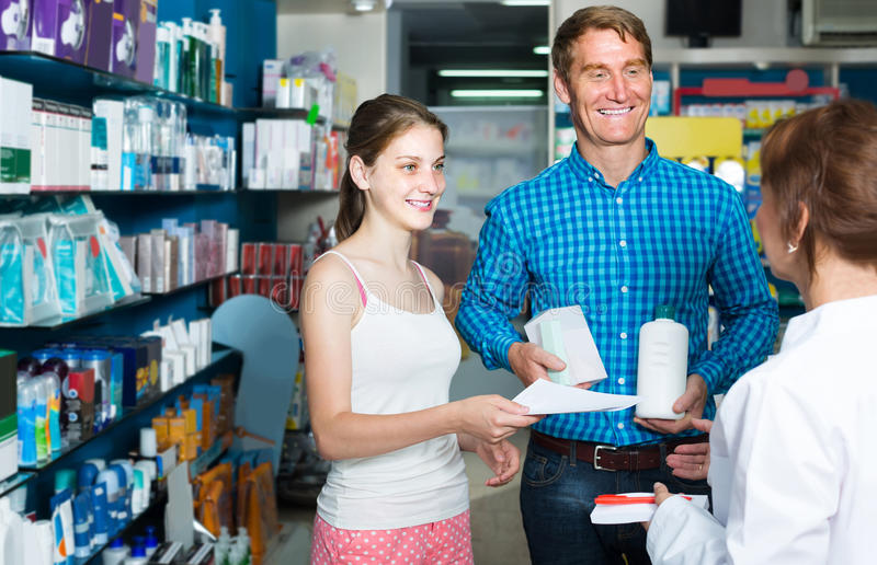 Portrait of man with daughter teenager shopping medicine in drug stock photo