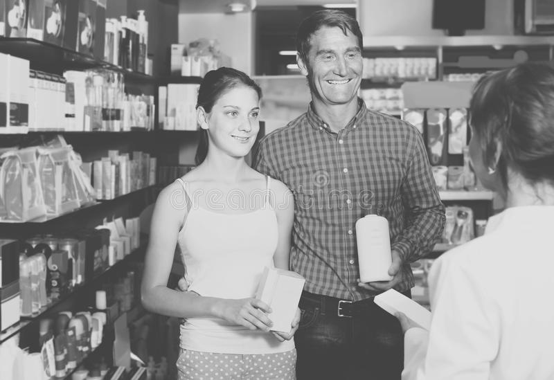 Portrait of man with daughter teenager shopping medicine in drug. Portrait of glad european men with daughter teenager shopping medicine in drug store stock photo