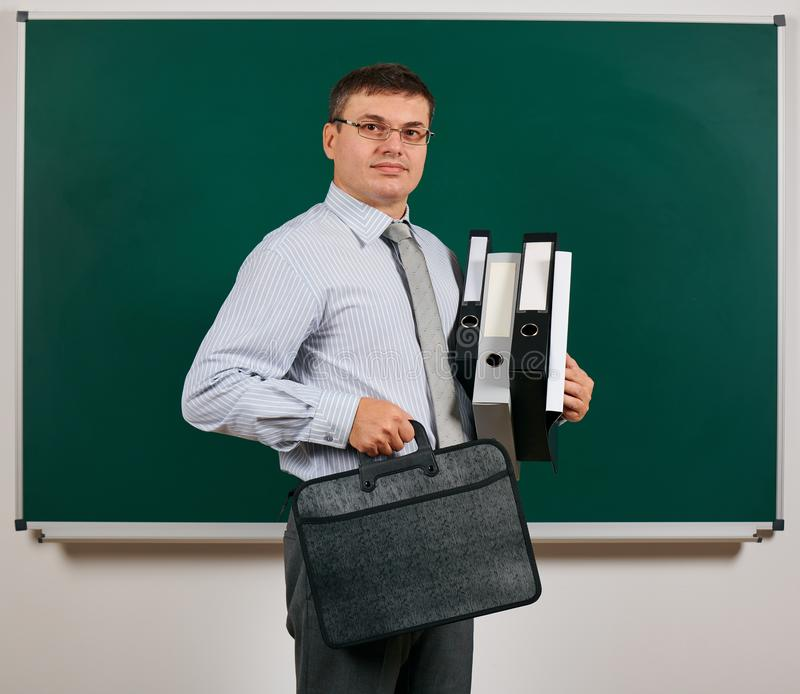 Portrait of a men dressed in business suit with folders, documents and briefcase, posing at blackboard background - learning and. Portrait of a man dressed in stock photo