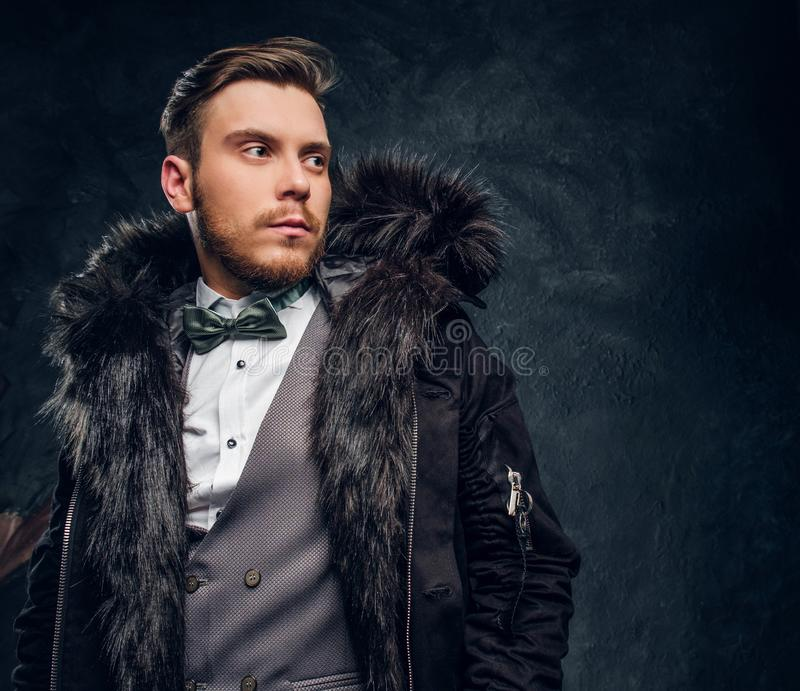 Portrait of a man dressed in an elegant suit and coat with a fur hood against a dark textured wall royalty free stock photo