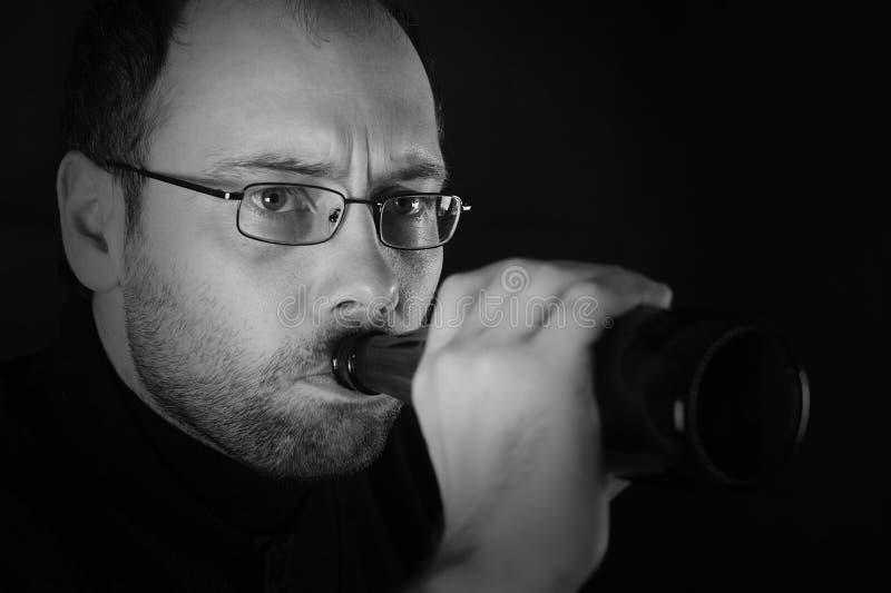 Portrait of man drinking beer in black