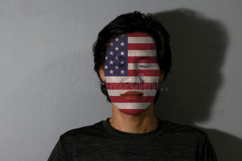 Portrait of a man with the flag of the America painted on his face and close eyes with black shadow on grey background. stock photo