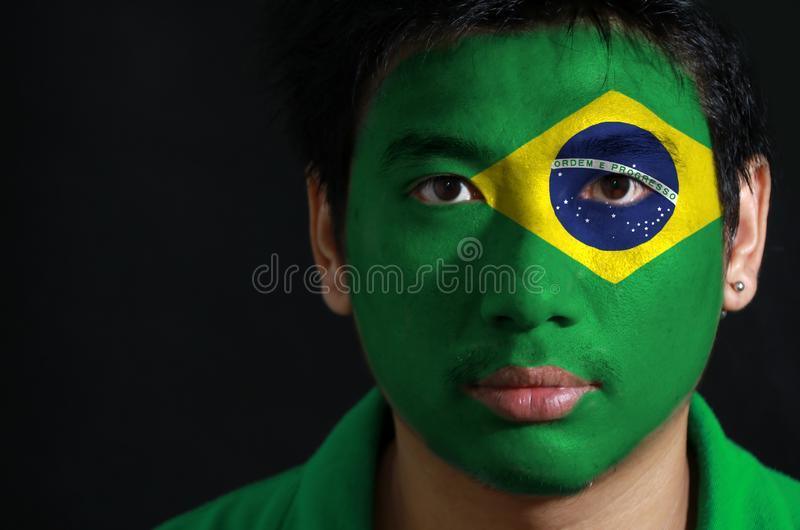 Portrait of a man with the flag of the Brazil painted on his face. stock images