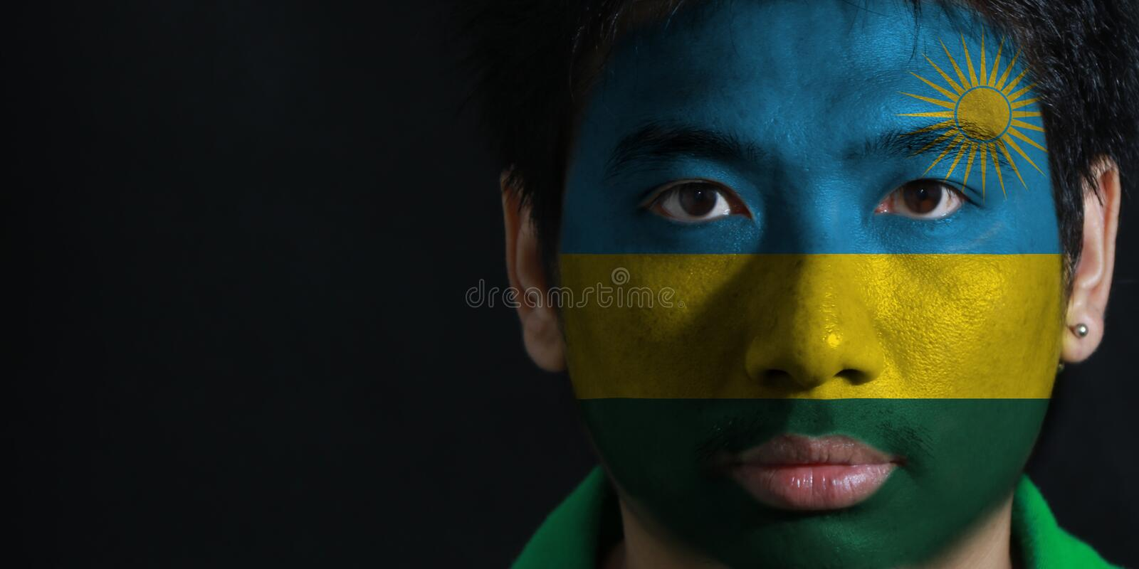 Portrait of a man with the flag of the Rwanda painted on his face on black background. royalty free stock image