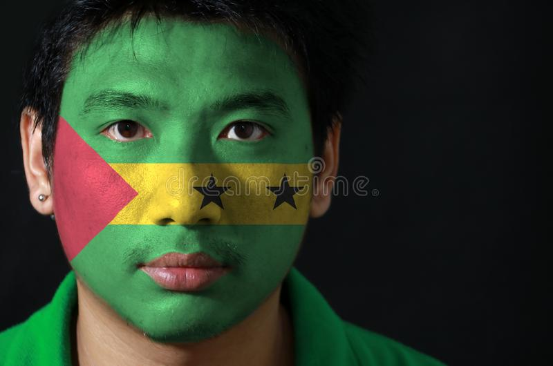 Portrait of a man with the flag of the Sao Tome and Principe painted on his face on black background. royalty free stock photos