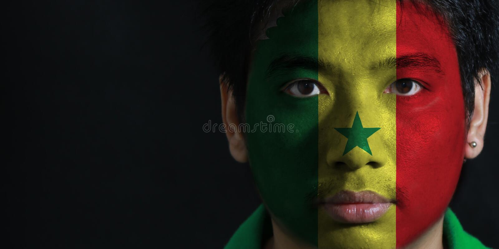 Portrait of a man with the flag of the Senegal painted on his face on black background. stock photos