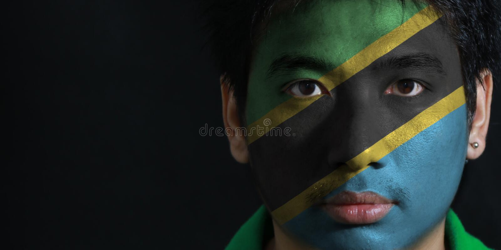 Portrait of a man with the flag of the Tanzania painted on his face on black background. stock photography