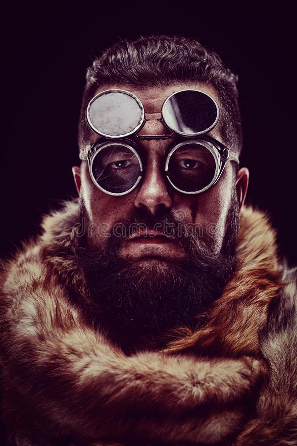 Portrait of a man in a fur coat wearing goggles royalty free stock photography